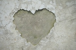 Heart shaped crack on the wall revealing the inner cement texture