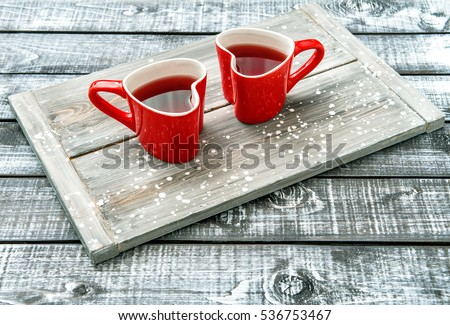 Heart shaped cups with red drink on rustic wooden background. Valentines day #536753467