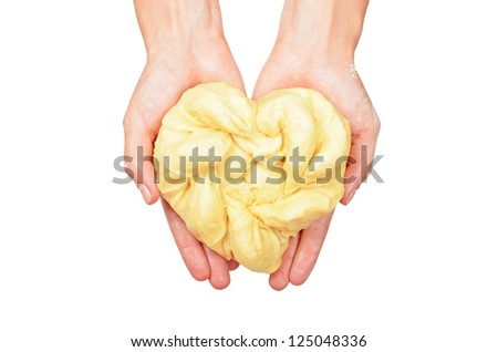 Heart shaped dough in woman hand, isolated on white background