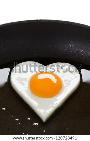 heart shaped egg cooking in a frying pan