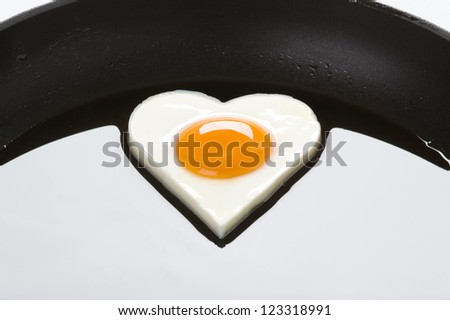 heart shaped egg in a frying pan