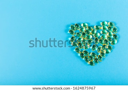 Heart shaped fish oil capsules on blue background