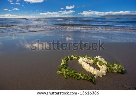 Heart shaped flower lei and leaf garland (wedding leis) on a tropical beach