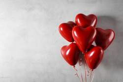 Heart shaped foil balloons on concrete wall background