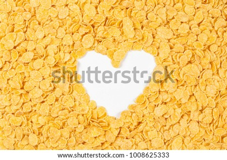 Heart shaped frame of cornflakes on a white background. Cornflakes scattered on a table. Close up top view textures #1008625333