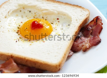 Heart shaped fried egg in toast - stock photo
