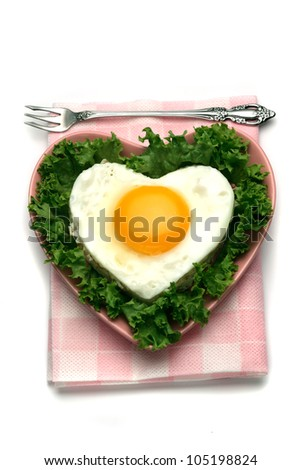 Heart shaped fried egg with salad leaves isolated on white background / heart shaped food