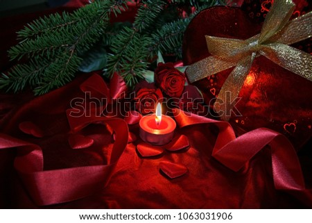 Heart shaped gift box, spruce branch, red hearts, red roses on a red satin background. New Year, Christmas Celebration. #1063031906