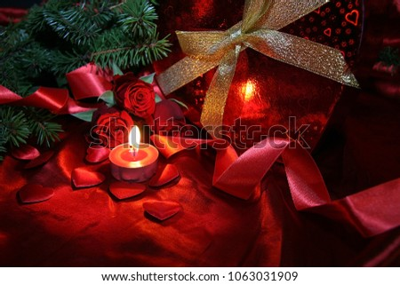 Heart shaped gift box, spruce branch, red hearts, red roses on a red satin background. New Year, Christmas Celebration. #1063031909
