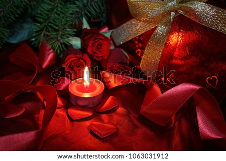 Heart shaped gift box, spruce branch, red hearts, red roses on a red satin background. New Year, Christmas Celebration. #1063031912