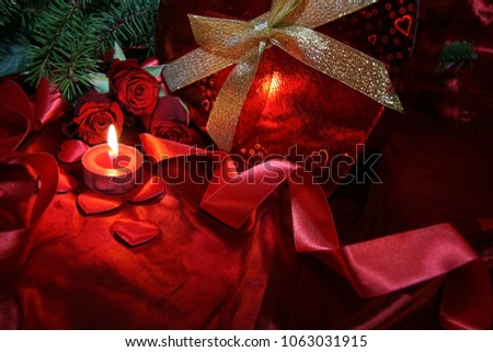 Heart shaped gift box, spruce branch, red hearts, red roses on a red satin background. New Year, Christmas Celebration. #1063031915