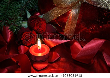 Heart shaped gift box, spruce branch, red hearts, red roses on a red satin background. New Year, Christmas Celebration. #1063031918