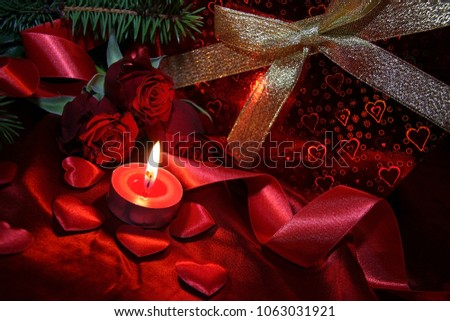 Heart shaped gift box, spruce branch, red hearts, red roses on a red satin background. New Year, Christmas Celebration. #1063031921