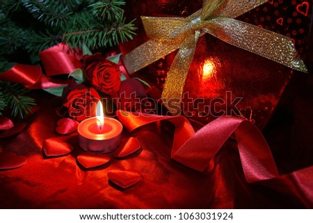 Heart shaped gift box, spruce branch, red hearts, red roses on a red satin background. New Year, Christmas Celebration. #1063031924