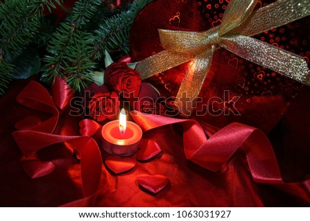 Heart shaped gift box, spruce branch, red hearts, red roses on a red satin background. New Year, Christmas Celebration. #1063031927