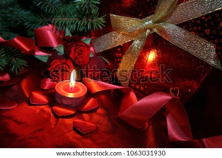 Heart shaped gift box, spruce branch, red hearts, red roses on a red satin background. New Year, Christmas Celebration. #1063031930