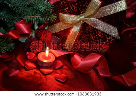 Heart shaped gift box, spruce branch, red hearts, red roses on a red satin background. New Year, Christmas Celebration. #1063031933