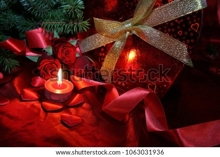 Heart shaped gift box, spruce branch, red hearts, red roses on a red satin background. New Year, Christmas Celebration. #1063031936
