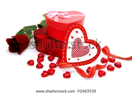 Heart-shaped gift boxes with Valentines Day rose, gems and ribbon over a white background
