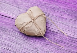 Heart shaped gift on purple wooden background