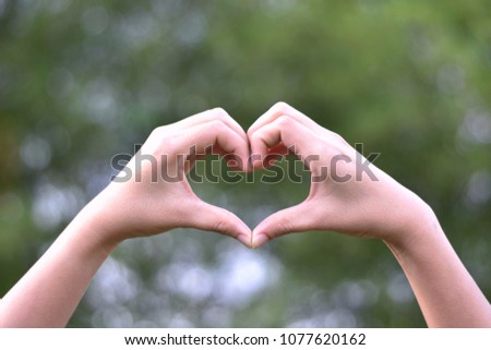 Heart-shaped hand Bokeh background of nature #1077620162