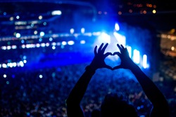 Heart shaped hands at concert, loving the artist and the festival. Music concert with lights and silhouette of a man partying