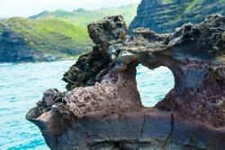 Heart shaped hole in a rock overlooking the ocean Maui Hawaii