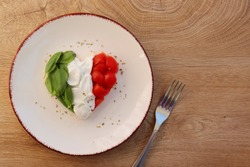 Heart shaped Italian Caprese Salad arranged by Italian basil,buffalo mozzarella and tomatoes look like Italian Flag on plate with wooden table background.Love Italian food concept for Valentine day