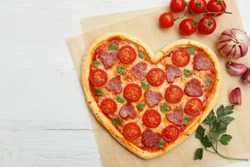 Heart shaped Italian pizza with salami,cherry tomatoes,garlics,parsley,pizza sauce and mozzella on parchment paper with white wood table background.Love concept for Valentine's day.Top view