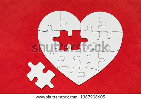 Heart-shaped jigsaw puzzle on color background. Puzzle heart on wooden background. A missing piece of the heart puzzle. Heart shape jigsaw puzzle. Puzzles in the shape of a heart.