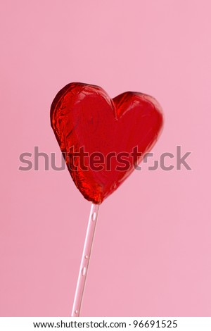 Heart-shaped lollipop isolated on pink background #96691525