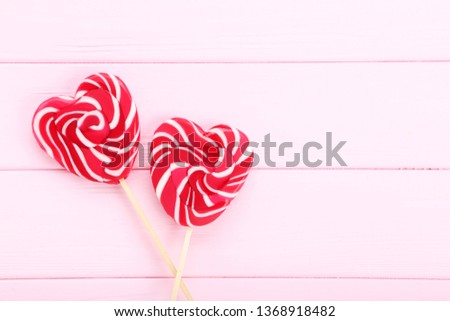 Red sugar heart-shaped lollipop on the wooden table Images and Stock