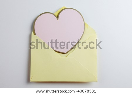 Heart shaped note in envelope on the plain background
