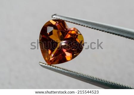 Heart shaped orange topaz gemstone held by tweezers.