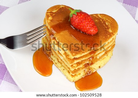 Heart-shaped pancakes with syrup and a strawberry on a white dish. A perfect breakfast for Valentine's Day