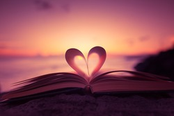 Heart shaped paper book against a beautiful sunset.