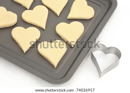 Heart shaped pastry dough on a baking tray with metal cookie cutter, over white background.