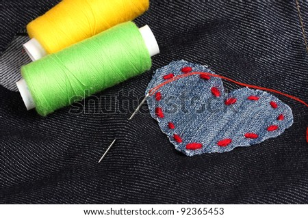 Heart-shaped patch on jeans with threads and needle closeup