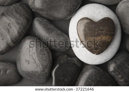 Heart shaped pebble framed on a dark pebble background - stock photo