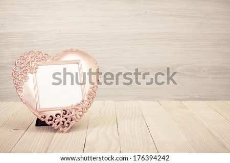 Heart shaped photo frame on wooden table
