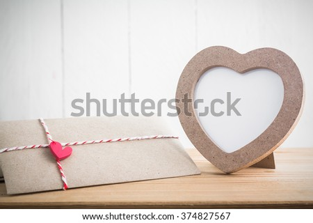 Heart shaped photo frame with envelope on wood table