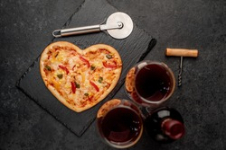 heart shaped pizza and bottle of red wine, glasses on stone background. valentine's day celebration concept