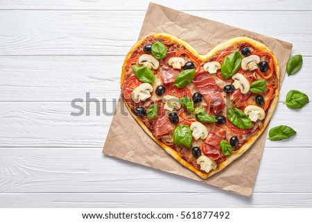 Heart shaped pizza delicious love concept Valentine's Day romantic restaurant dinner Italian food. Olives, prosciutto, champignons, tomatoes and mozzarella meal served on white wooden table background
