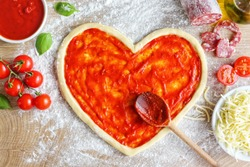 Heart shaped pizza dough covered with pizza sauce on wooden table  with cherry tomatoes,tomato sauce,mozzarella cheeses,salami,olive oil and basil leaves.Cooking with love concept for Valentine's day