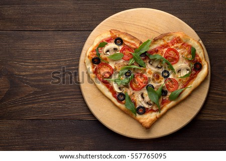 Shutterstock Heart shaped pizza on cutting board on wooden table. Romantic dish for Valentines day. Top view, copy space.
