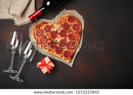 Heart shaped pizza with mozzarella, sausagered, wine bottle, two wineglass, gift box on rusty background. Top view. #1253225842