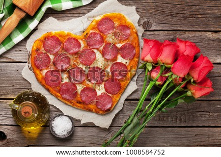 Heart shaped pizza with pepperoni and mozzarella and red rose flowers bouquet. Valentines day greeting card. #1008584752