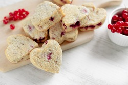 Heart shaped red currant scones, healthy sweet coconut flour cookies on wooden cutting board and white table surface, Valentine's Day sweet treats front close up