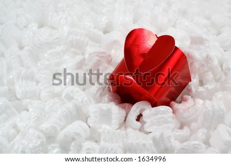 Heart shaped red gift box in white packing material