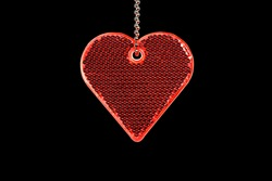 Heart shaped reflector on chain isolated on black background. The reflector is visible in the headlights of cars. Wearing a reflector can save life.